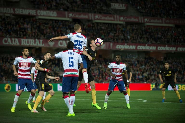 Granada's Sverrir Ingi Ingason vies with Atletico Madrid's Diego Godin (3rdR) during their Spanish league football match in Granada on March 11, 2017