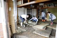 Local residents try to clean inside a house at an area flooded by Typhoon Hagibis in Marumori