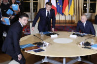 French President Emmanuel Macron, center, Russian President Vladimir Putin, right, and Ukrainian President Volodymyr Zelenskiy, left, sit before a working session with German Chancellor Angela Merkel at the Elysee Palace Monday, Dec. 9, 2019 in Paris. Russian President Vladimir Putin and Ukraine's president are meeting for the first time at a summit in Paris to find a way to end the five years of fighting in eastern Ukraine. (AP Photo/Thibault Camus, Pool)