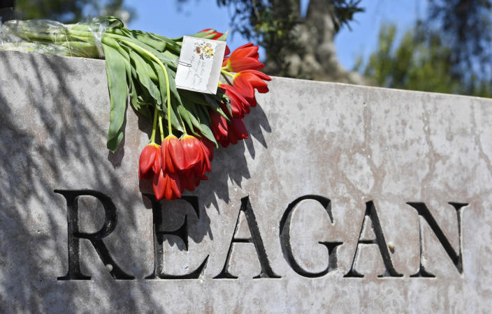 <p>Flowers are draped atop the sign at the entrance to the Ronald Reagan Presidential Library on Sunday in honor of former first lady Nancy Reagan. <i><i>(Photo: Mark J. Terrill/AP)</i></i></p>