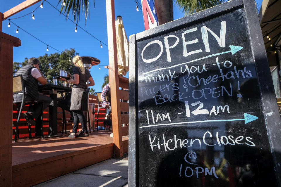 A sign saying open is displayed outside a restaurant along the Coast Highway 101 in Encinitas, Calif., on Friday, Dec. 18, 2020. (AP Photo/Ringo H.W. Chiu)