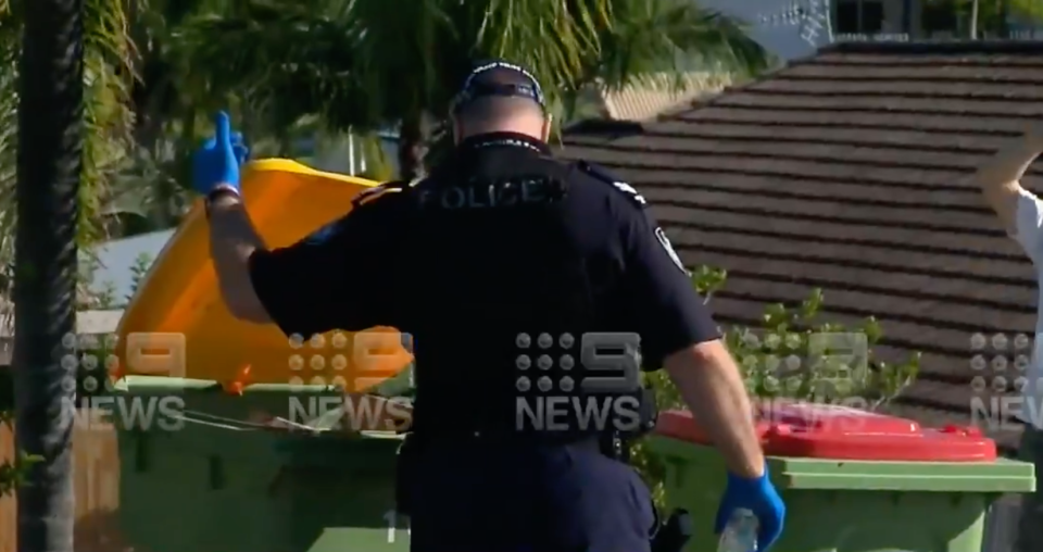A police officer checks nearby bins for potential evidence. Source: Nine News