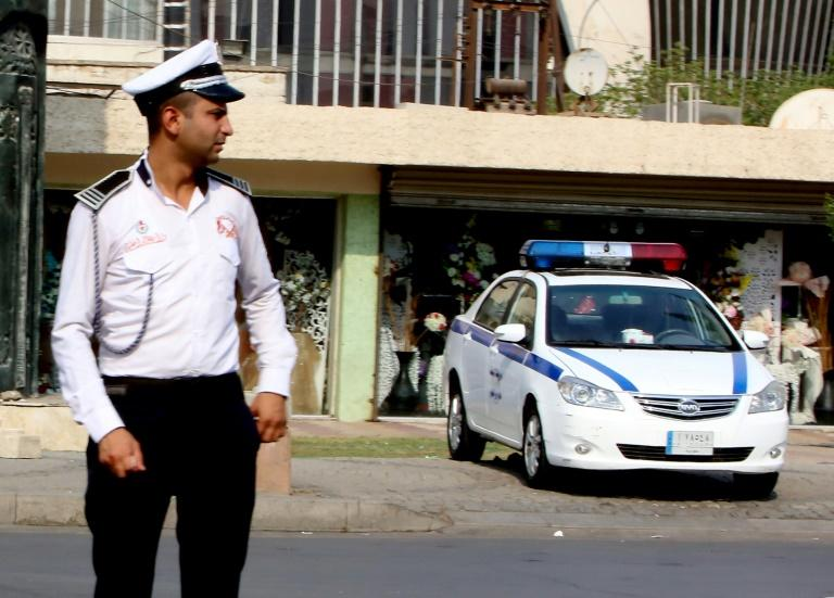 An Iraqi policeman stands in a street of Baghdad where tradition holds that many cases are settled by tribal mediation rather than the law of the land