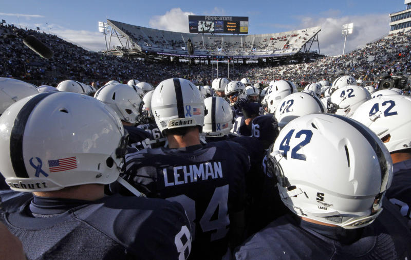 FILE - In this Nov. 24, 2012, file photo Penn State players huddle on the field before an NCAA college football game against Wisconsin in State College, Pa. Penn State said about 90 percent of the $7.8 million decline in revenue for the athletic department was due to a loss of one-time fees related to football season-ticket renewals that were not budgeted for in 2012.  (AP Photo/Gene J. Puskar, File)