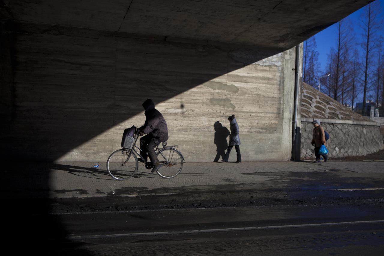 North Koreans pedestrians pass under a bridge in Pyongyang on Friday, Feb. 15, 2013. (AP Photo/David Guttenfelder)