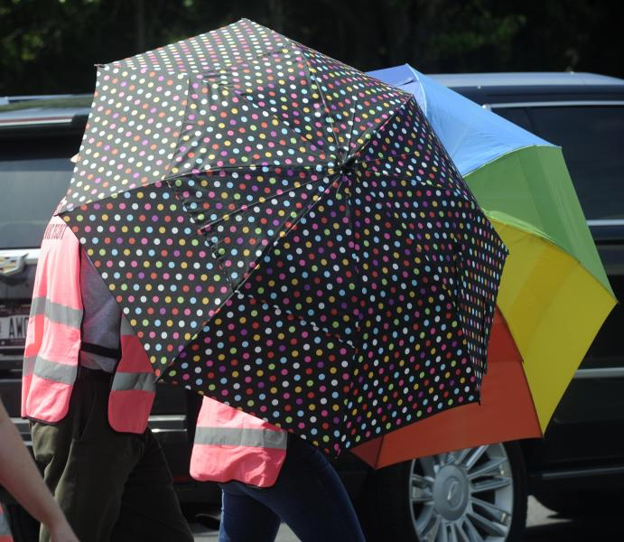 Escorts, using umbrellas, shield clients from the gestures and voices of anti-abortion activists standing on the sidewalk in front of the Alabama Women's Wellness Center Friday, May 17, 2019 in Huntsville, Ala. The Alabama legislation signed into law Wednesday would make performing or attempting to perform an abortion at any stage of pregnancy a felony. The ban does not allow exceptions for rape and incest.(AP Photo/Eric Schultz)