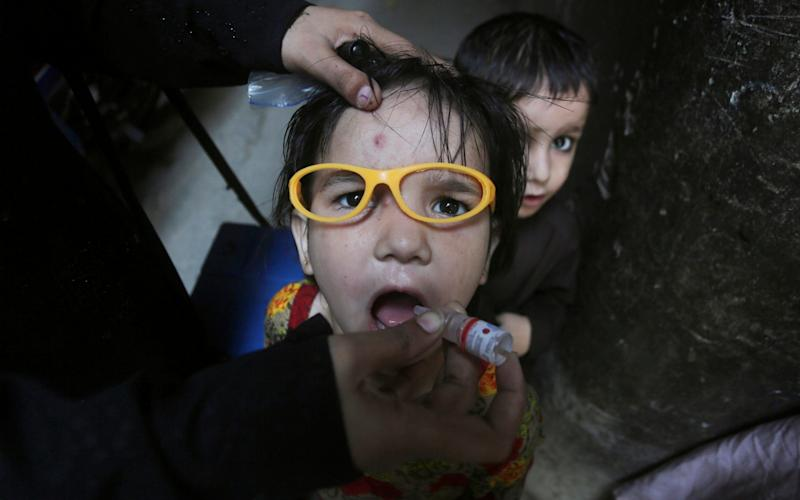 A health worker gives a polio vaccination to a child in Lahore, Pakistan - AP Photo/K.M. Chaudary