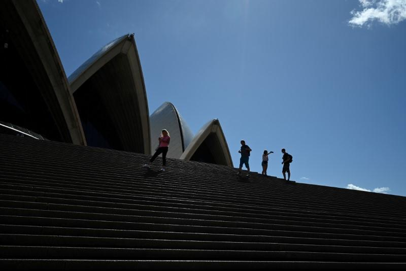 FILE PHOTO: A handful of tourists stand atop the mostly deserted steps of the Sydney Opera House in Sydney