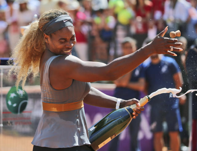 Serena Williams sprays sparkling wine as she celebrates after winning the final against Italy's Sara Errani at the Italian Open tennis tournament, in Rome, Sunday, May 18, 2014. Serena Williams kept the crowd from being a factor in a 6-3, 6-0 victory over 10th-seeded Sara Errani to win the Italian Open for the third time Sunday. (AP Photo/Gregorio Borgia)