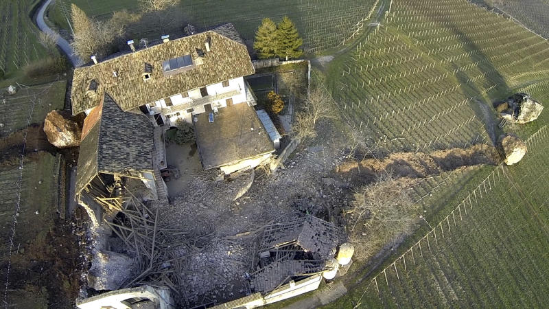 In this photo provided by Tareom.com Thursday, Jan. 30, 2014, and taken on Jan. 23, 2014, a huge boulder is seen after it missed a farm house by less than a meter, destroying the barn, and stopped in the vineyard, while the second giant boulder at left, which detached during the same landslide on Jan. 21, 2014, stopped next to the house, in Ronchi di Termeno, in Northern Italy. According to reports, the Trebo family living there was unharmed in the landslide. (AP Photo/Markus Hell, Tareom.com, ho)