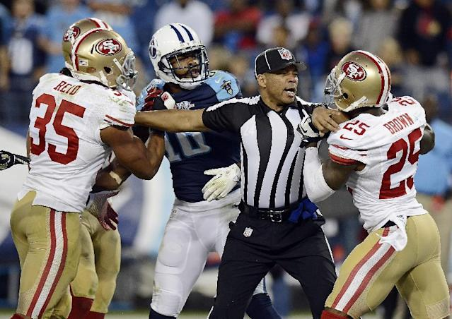 Back judge Greg Steed tries to separate San Francisco 49ers cornerback Tarell Brown (25) and Tennessee Titans wide receiver Kenny Britt (18) during a scuffle in the fourth quarter of an NFL football game on Sunday, Oct. 20, 2013, in Nashville, Tenn. At left is 49ers' Eric Reid (35). (AP Photo/Mark Zaleski)