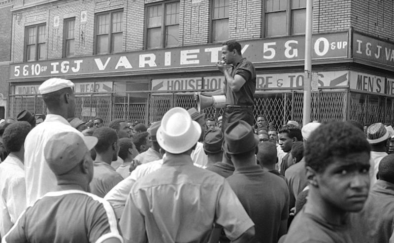 During a lethal riot in Detroit in July 1967, Rep. John Conyers uses a bullhorn to urge residents to return to their homes.