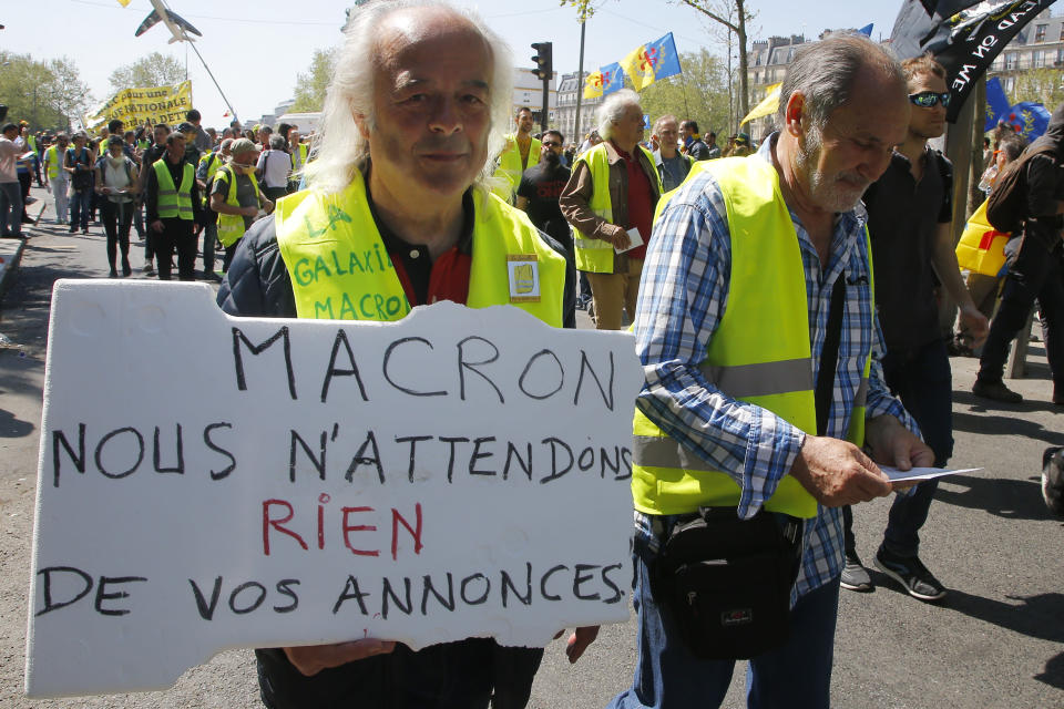 A man holds a sign which reads 'Macron, we don't expect anything from your advertisements' during a yellow vest demonstration in Paris, Saturday, April 20, 2019. French yellow vest protesters are marching anew to remind the government that rebuilding the fire-ravaged Notre Dame Cathedral isn't the only problem the nation needs to solve. (AP Photo/Michel Euler)