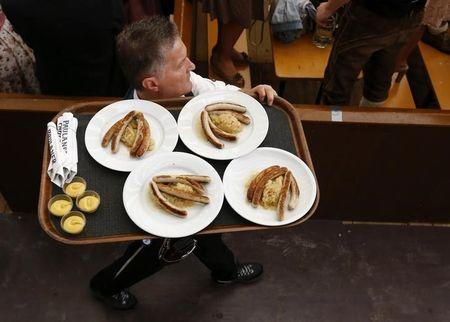 A waiter carries plates with sausages in a tent during the 182nd Oktoberfest in Munich
