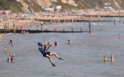 A person takes a ride on a zip wire from the pier to the beach in Bournemouth, Dorset - Credit: Andrew Matthews