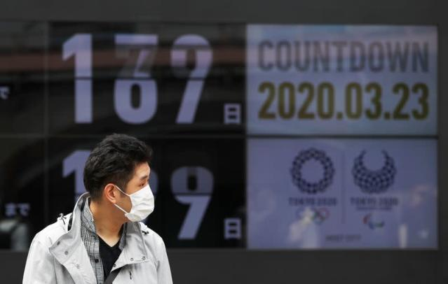 A passersby, wearing a face mask due to the outbreak of the coronavirus disease (COVID-19), walks past a screen counting down the days to the Tokyo 2020 Olympic Games