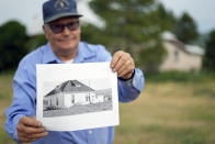 Third-generation rancher Jim Stanko poses for a photo, Tuesday, July 13, 2021, in front of his childhood home near Steamboat Springs, Colo., as he holds a picture of the home taken in 1937. The family now rents out the home for supplemental income to support their cattle ranch, which is being threatened by high feed prices and severe drought conditions that have affected hay harvest. (AP Photo/Brittany Peterson)