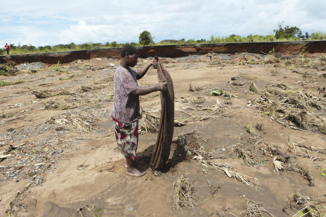A villager sulvages what remains of a piece of clothing near a section of the road damaged by Cyclone Idai in Nhamatanda about 50 kilometres from Beira, in Mozambique, Friday March, 22, 2019. As flood waters began to recede in parts of Mozambique on Friday, fears rose that the death toll could soar as bodies are revealed. (AP Photo/Tsvangirayi Mukwazhi)
