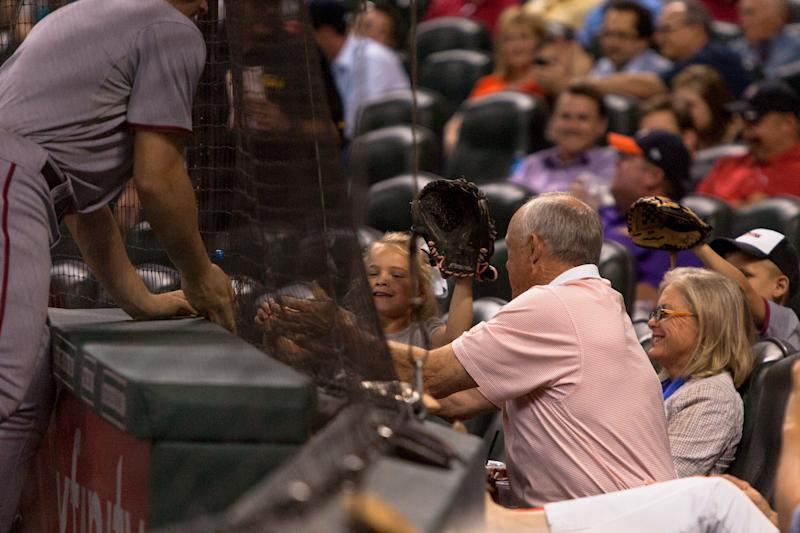 APRIL 29 2014: Former Houston Astros pitcher Nolan Ryan reaches underneath the net to retrieve a foul ball for a young fan during the game against the Washington Nationals. Washington Nationals defeated Houston Astros 4-3 at Minute Maid Park in Houston, TX. (Photo by Juan DeLeon/Icon SMI/Corbis via Getty Images)