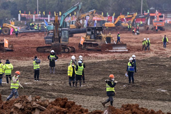 Workers carry materials at the construction site of a new hospital being built to treat patients from a deadly virus outbreak in Wuhan (Picture: AFP/Getty)