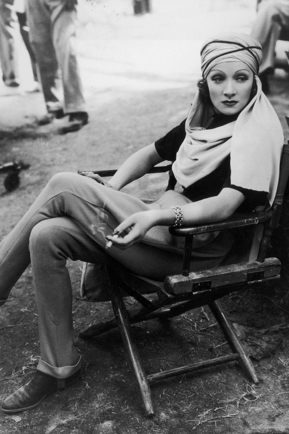 <p>Marlene Dietrich takes a smoke break while wearing a turban for her role in <em>The Garden of Allah. </em></p>