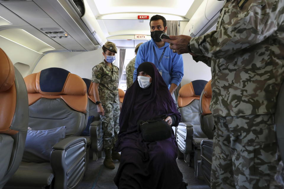 """An Albanian woman, center, boards a plane, during an operation to take home five Albanians from al-Hol, northern Syria, in Beirut, Lebanon, Tuesday, Oct. 27, 2020. The repatriation of four children and a woman related to Albanian nationals who joined Islamic extremist groups in Syria """"is a great step"""" to be followed by more repatriations, Albania's prime minister said Tuesday in Beirut. (AP Photo/Bilal Hussein)"""