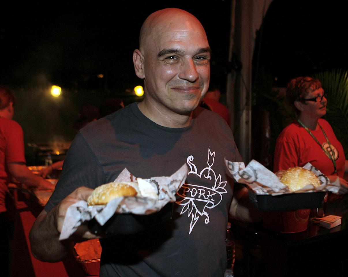 Michael Symon holds his Porky Burgers during the Burger Bash at the Food Network South Beach Wine & Food Festival in Miami Beach, Fka., on Friday, Feb. 24, 2012. (AP photo/Jeffrey M. Boan)
