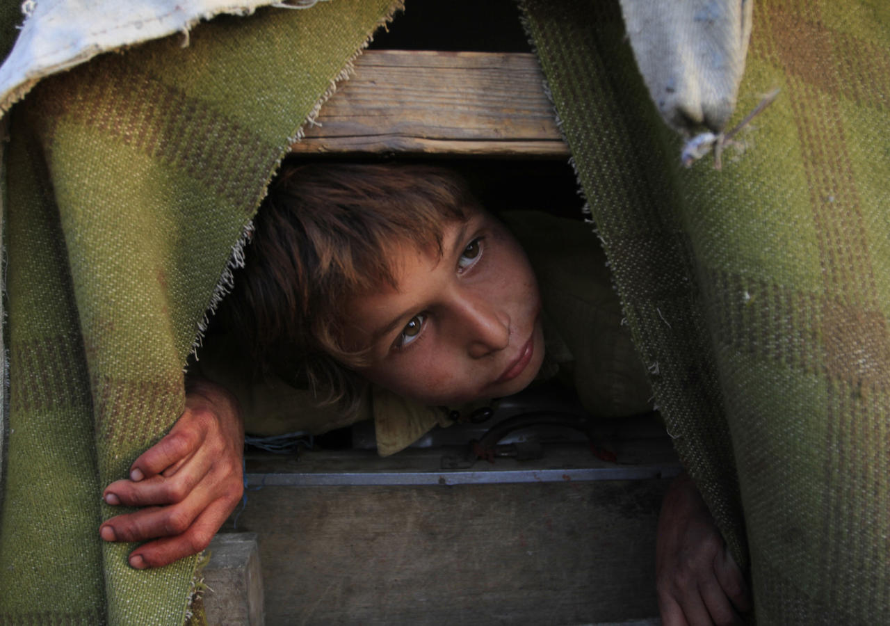 <p>An Afghan refugee boy Gul Zaman who fled from Afghanistan with his family, peeps from his make-shift tent in the outskirts of Karachi, Pakistan on March 13, 2012. (AP Photo/Shakil Adil) </p>