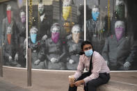 FILE - In this Wednesday, Dec. 9, 2020, file photo, a man takes a coffee break in front of a COVID 19-themed mural, in Beverly Hills, Calif. On Monday, Oct. 11, 2021, California's coronavirus death toll reached 70,000. (AP Photo/Marcio Jose Sanchez, File)