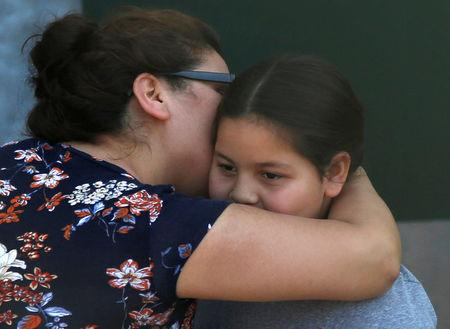 A student who was evacuated after a shooting at North Park Elementary School is embraced after groups of them were reunited with parents waiting at a high school in San Bernadino