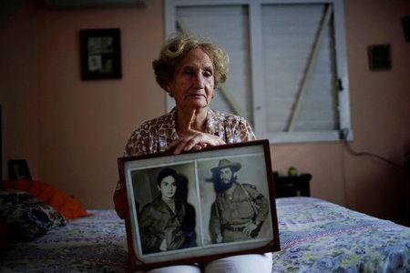 Former rebel Juana Ramirez, 81, poses for a picture holding a photograph of her with her late husband and rebel fighter Luiz Perez, Havana, Cuba, April 4, 2018. REUTERS/Alexandre Meneghini