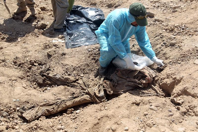 Iraqi security forces inspect a mass grave containing the remains of dozens of people believed to have been slain by jihadists in the city of Tikrit, on April 12, 2015 (AFP Photo/Ahmad al-Rubaye)