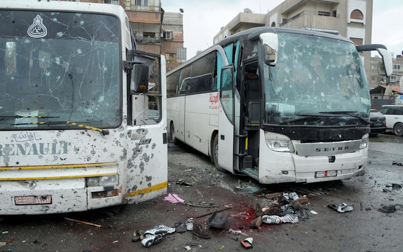 Blood and shoes were scattered on the ground in front of the two buses used by Iraqi pilgrims to Syria - EPA/SANA