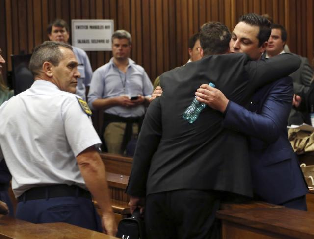 "Olympic and Paralympic track star Oscar Pistorius hugs his brother Carl Pistorius (facing camera) during his trial at the North Gauteng High Court in Pretoria, March 3, 2014. The first witness at Oscar Pistorius' murder trial told the court on Monday she heard ""bloodcurdling screams"" from a woman followed by shots, a dramatic opening to a case that could see one of global sports' most admired role models jailed for life. Oscar Pistorius pleaded not guilty to murdering his girlfriend, model Reeva Steenkamp, on Valentine's Day last year. REUTERS/Themba Hadebe/Pool (SOUTH AFRICA - Tags: SPORT ATHLETICS ENTERTAINMENT CRIME LAW)"