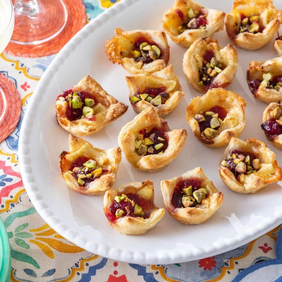"""<p>This twist on the classic brie en croute appetizer (or wrapped baked brie) comes in a hand-held mini size that's not just adorable, but tasty, too! </p><p><strong><a href=""""https://www.thepioneerwoman.com/food-cooking/recipes/a37261373/cranberry-brie-bites-recipe/"""" rel=""""nofollow noopener"""" target=""""_blank"""" data-ylk=""""slk:Get the recipe."""" class=""""link rapid-noclick-resp"""">Get the recipe.</a> </strong></p>"""