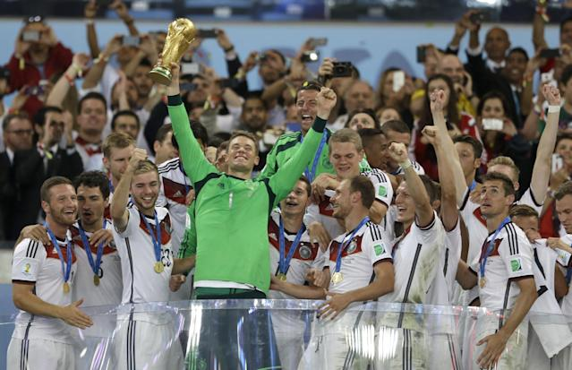 Germany's goalkeeper Manuel Neuer holds up the World Cup trophy as the team celebrates their 1-0 victor over Argentina after the World Cup final soccer match between Germany and Argentina at the Maracana Stadium in Rio de Janeiro, Brazil, Sunday, July 13, 2014. (AP Photo/Natacha Pisarenko)