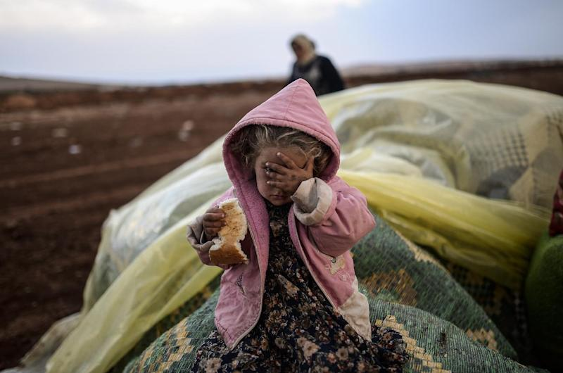 A Syrian Kurdish woman wait with her daughter near the Syria border at the southeastern town of Suruc after crossing the border between Syria and Turkey (AFP Photo/Bulent Kilic)