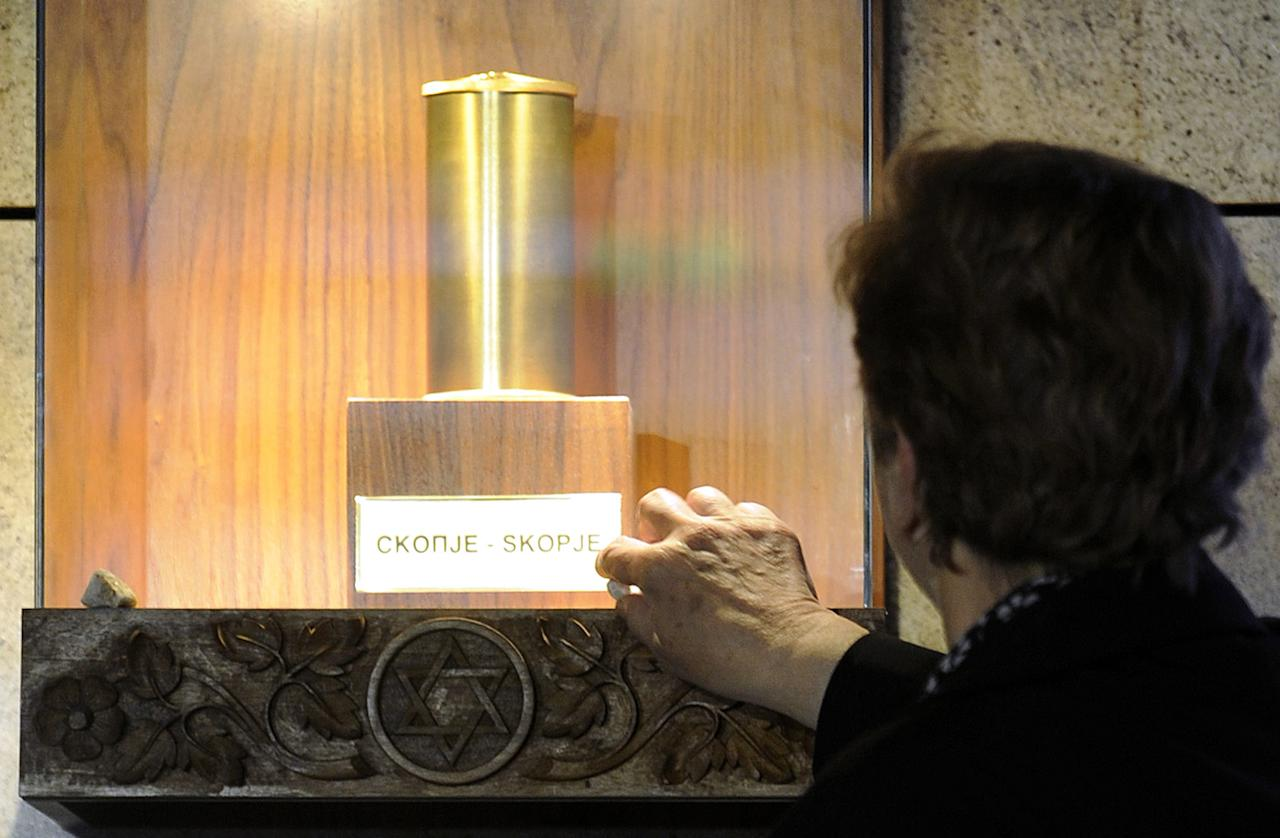 A woman places a small rock at an urn with ashes in memory of victims of the Holocaust, in the Holocaust Memorial center of the Jews of Macedonia in the country's capital Skopje, on Thursday, April 19, 2012. Macedonia is marking an annual remembrance day for the six million Jews killed by the Nazis in World War II. (AP Photo/Boris Grdanoski)