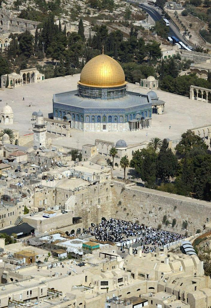This is an aerial view of the golden Dome of the Rock Mosque at the Al Aqsa Mosque compound, known by the Jews as the Temple Mount, top, as Jewish worshipers pray at the Western Wall, bottom, in east Jerusalem's Old City is seen in this  Oct 4 2004 photo. Israel will limit the number of Muslim worshippers at Islam's third holiest shrine to 60,000 during the holy month of Ramadan, the police minister said Wednesday,  Oct 13 2004 citing concerns that part of the compound could collapse under a larger number of visitors. (AP Photo/Oded Balilty) ORG XMIT: JRL115