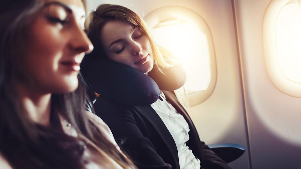 Girlfriends traveling by plane. A female passenger sleeping on neck cushion in airplane