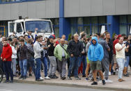 "People gather during a rally against the results of the country's presidential election outside the Belarusian Automobile Plant (BelAZ) in Zhodino, about 50 km (31 miles) north-east of Minsk, Belarus, Thursday, Aug. 13, 2020. Hundreds of people were back on the streets of Belarus' capital on Thursday morning, forming long ""lines of solidarity"" in protest against an election they say was rigged to extend the rule of the country's authoritarian leader and against a crackdown on rallies that followed the vote. (AP Photo/Sergei Grits)"