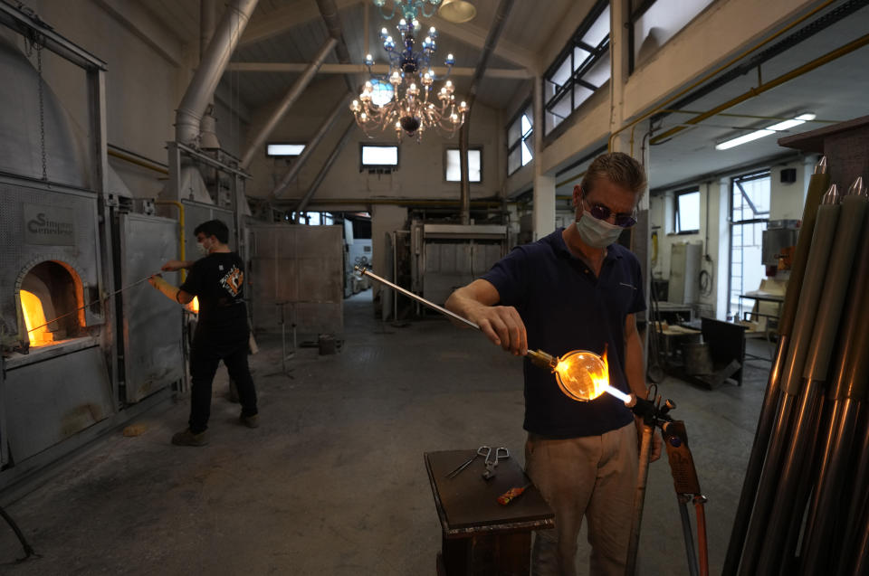 A glass-worker finishes a glass artistic creation in a factory in Murano island, Venice, Italy, Thursday, Oct. 7, 2021. The glassblowers of Murano have survived plagues and pandemics and have transitioned to highly prized artistic creations to outrun competition from Asia, but surging energy prices may be their doom. (AP Photo/Antonio Calanni)