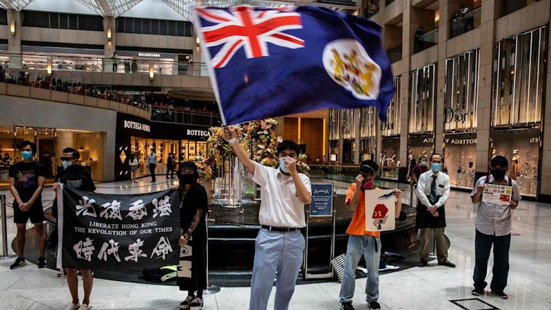 A protester waves a British colonial flag