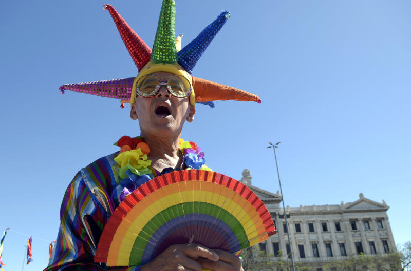 An activist wearing gay pride colors stands outside Parliament where lawmakers are debating a same sex marriage law in Montevideo, Uruguay, Tuesday, Dec. 11, 2012. Taboo-breaking Uruguay is poised to legalize gay marriage, with lawmakers debating Tuesday whether to create a single law governing marriage for heterosexuals and homosexuals. The new proposal would make Uruguay the second nation in Latin America and the 12th in the world to legalize gay marriage, after The Netherlands, Belgium, Spain, Canada, South Africa, Norway, Sweden, Portugal, Iceland, Argentina and Denmark. (AP Photo/Matilde Campodonico)
