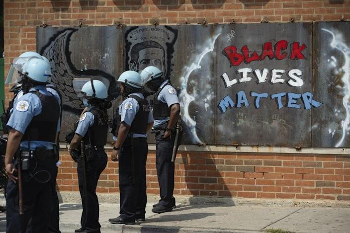 Police officers stand beside a mural for George Floyd in the Chicago neighborhood of Bronzeville during an anti-police brutality protest. (Pat Nabong/Chicago Sun-Times via AP, File)