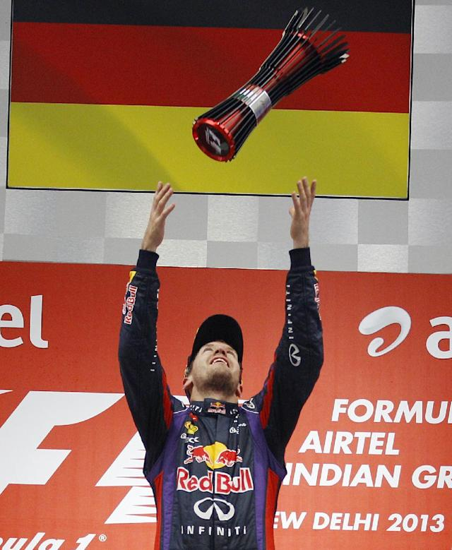 Red Bull driver Sebastian Vettel of Germany throws his trophy in the air after winning the Indian Formula One Grand Prix and his 4th straight F1 world championship at the Buddh International Circuit in Noida, India, Sunday, Oct. 27, 2013. (AP Photo/Aijaz Rahi)