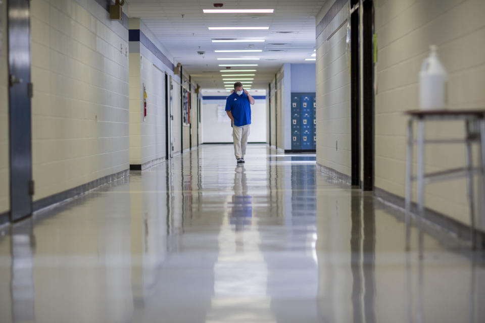 Johnson County Middle School Principal Reid Bethea walks the empty halls of his school as he speaks with one of his teachers to get an update on her CoVid symptoms, Friday, Aug., 20, 2021, in Wrightsville, Ga. A few weeks into the new school year, growing numbers of U.S. districts have halted in-person learning or switched to hybrid models because of rapidly mounting coronavirus infections. With 40% of students in quarantine or isolation, the Johnson County district shifted last week to online instruction until Sept. 13. (AP Photo/Stephen B. Morton)