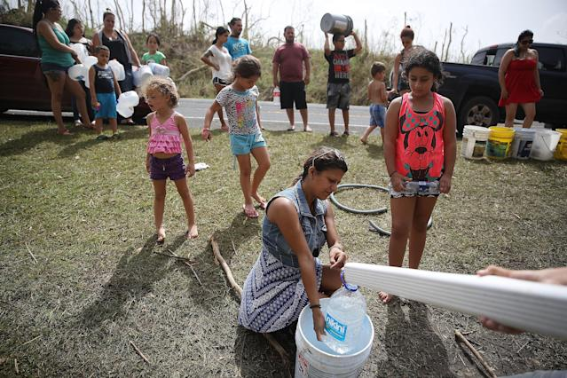 People in Corazal, Puerto Rico, fillcontainers with water from a natural spring on the side of the road as people deal with the aftermath of Hurricane Maria. (Joe Raedle via Getty Images)