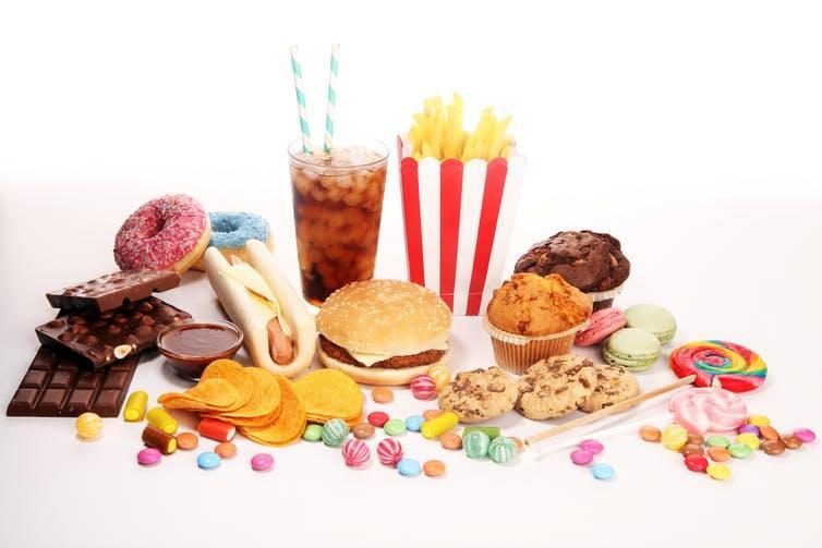 An assortment of unhealthy foods, including a hamburger, soda, crisps, chocolate, and candy.