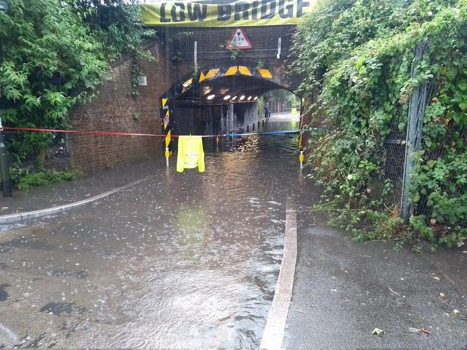 A flooded road in south London after heavy rainfall (PA Media)